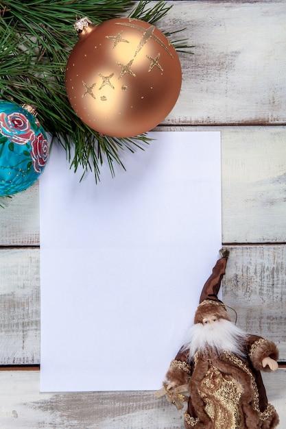 Das leere blatt papier auf dem holztisch mit weihnachtsschmuck. Kostenlose Fotos