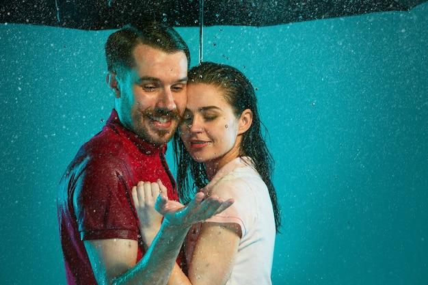 Das liebende paar im regen mit regenschirm auf einem türkisfarbenen hintergrund Kostenlose Fotos