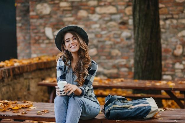 Das liebenswerte europäische weibliche model trägt lässige jeans und ein blaues hemd, die im warmen oktoberwochenende draußen sitzen Kostenlose Fotos