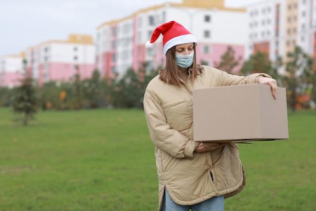 Das liefermädchen in einer roten weihnachtsmannmütze und einer medizinischen schutzmaske hält eine große kiste im freien. lieferung online-shop in quarantänezeit. Premium Fotos