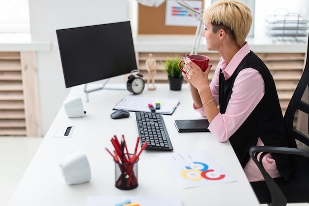 Das mädchen arbeitet im büro am computer und hält eine tasse. Premium Fotos