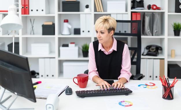 Das mädchen arbeitet im büro am computer. Premium Fotos
