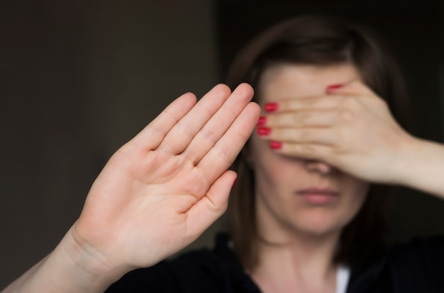 Das mädchen bedeckte ihr gesicht mit der hand und streckte die hand nach vorne Premium Fotos