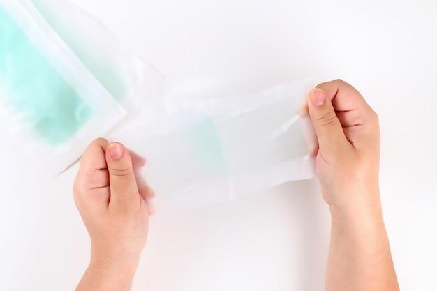 Das mädchen benutzt streifen für die enthaarung in ihren händen auf weiß. ansicht von oben. Premium Fotos
