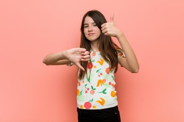 Das mädchen, das einen sommer trägt, kleidet gegen eine rote wand, welche die daumen oben und die daumen unten zeigt, wählen schwierig Premium Fotos