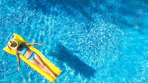 Das mädchen, das im swimmingpool sich entspannt, kind schwimmt auf aufblasbarer matratze und hat spaß im wasser auf familienurlaub, tropischer ferienort, luftbrummenansicht von oben Premium Fotos