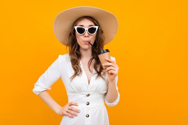 Das mädchen, das in einem weißen kleid mit einem hut i in den gläsern gekleidet wird, trinkt ein getränk auf einem gelben hintergrund Premium Fotos