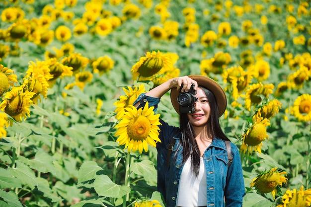 Das mädchen fotografiert gerne im sonnenblumenfeld. Kostenlose Fotos