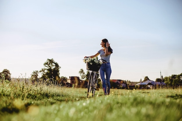 Das mädchen geht mit einem welpen auf einem gebiet in einem fahrrad hinter dem sonnigen licht Premium Fotos