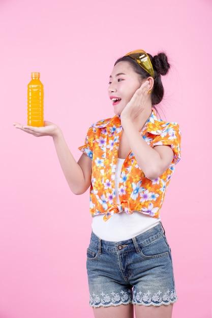 Das mädchen hält eine flasche orangensaft auf einem rosa hintergrund. Kostenlose Fotos