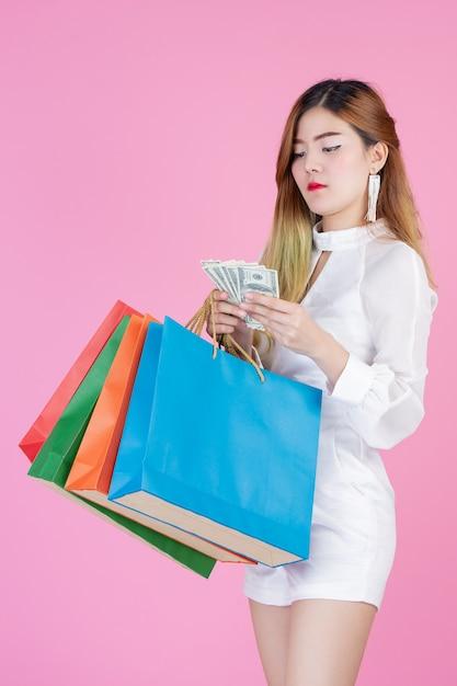 Das mädchen hält eine mode-einkaufstasche und hält eine dollarkarte Kostenlose Fotos