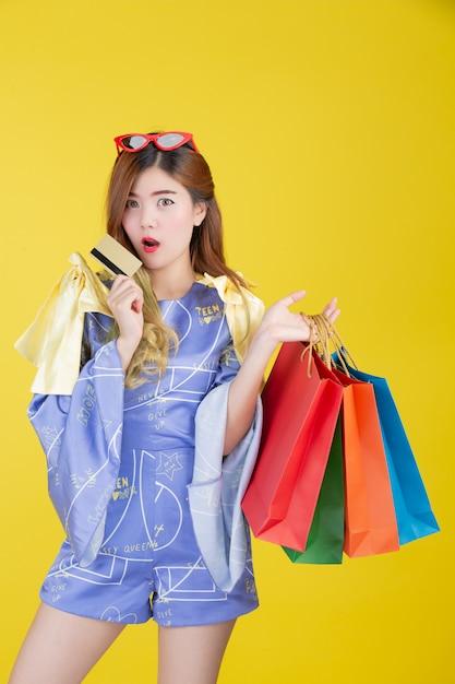 Das mädchen hält eine modeeinkaufstasche und hält eine chipkarte auf einem gelben hintergrund. Kostenlose Fotos