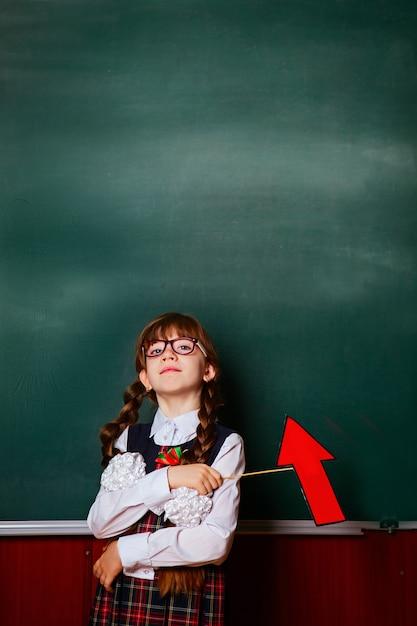 Das mädchen in der schuluniform steht auf einem hintergrund einer kalkhaltigen schulbehörde im klassenzimmer mit einem roten pfeil in den händen. Premium Fotos