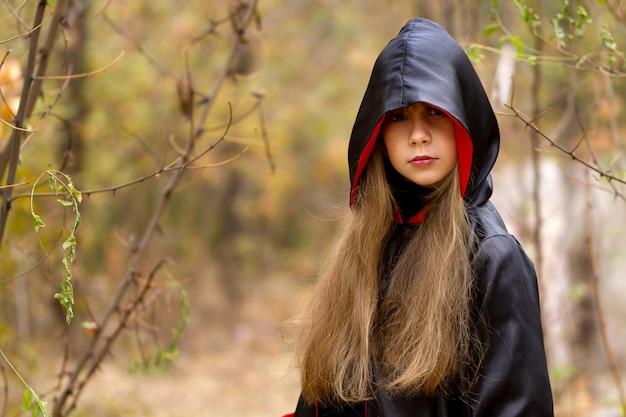 Das mädchen in einem roten und schwarzen umhang im wald Premium Fotos