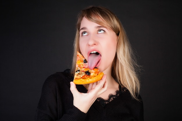 Das mädchen isst ein stück pizza und macht ein gesicht auf einem schwarzen hintergrund. Premium Fotos