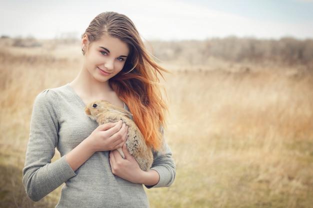 Das mädchen mit dem kaninchen glückliches kleines mädchen, das nettes flaumiges häschen hält Premium Fotos