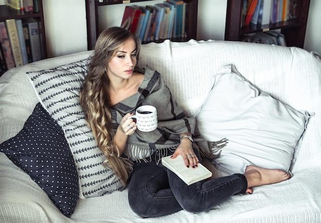 Das mädchen mit den langen haaren zog sich bequem an, las ein buch und trank kaffee auf der couch im hintergrund der bibliothek Kostenlose Fotos