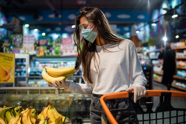 Das mädchen mit der op-maske wird bananen kaufen. Kostenlose Fotos