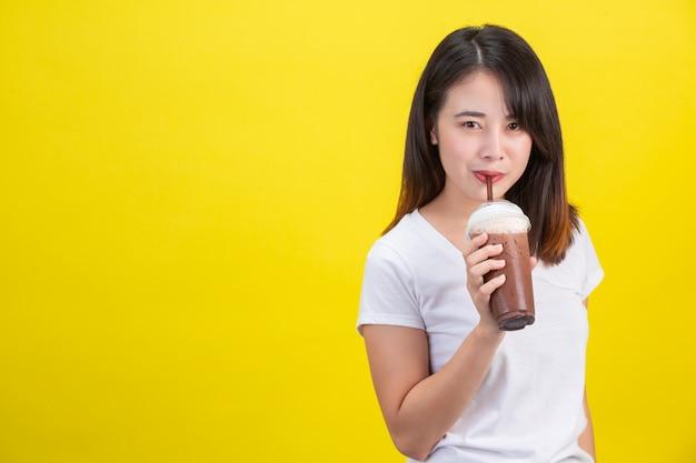 Das mädchen trinkt kaltes wasser aus kakao aus einem durchsichtigen plastikglas auf gelbem grund. Kostenlose Fotos