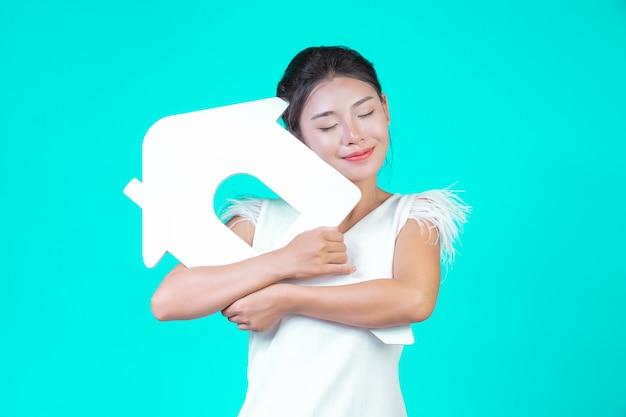 Das mädchen trug ein weißes langarmhemd mit blumenmuster, das das haussymbol hielt und verschiedene gesten mit einem blau zeigte. Kostenlose Fotos