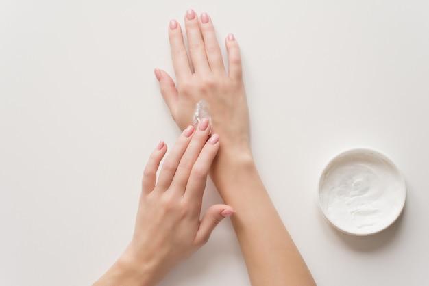 Das mädchen verteilt feuchtigkeitscreme auf ihren händen. Premium Fotos