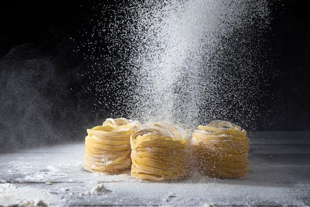 Das mehl wird durch ein sieb auf rohen tagliatelle-nudeln auf einem hölzernen küchentisch gesiebt. Premium Fotos