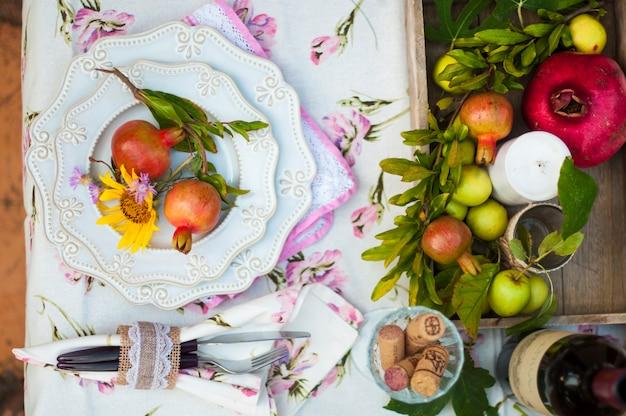 Das mittagessen ist romantisch im herbstgarten, urlaubsstimmung und gemütlichkeit. herbstliches abendessen im freien mit wein und obst. dekortisch mit blumen und granatapfel. altes foto. Premium Fotos
