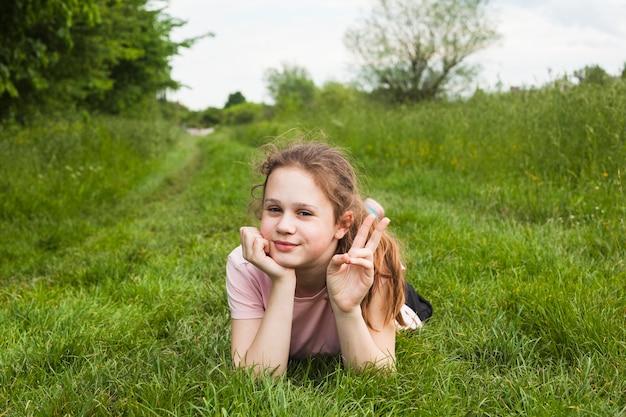 Das nette mädchen, das auf dem grasartigen land zeigt sieg liegt, unterzeichnen herein schöne natur Kostenlose Fotos