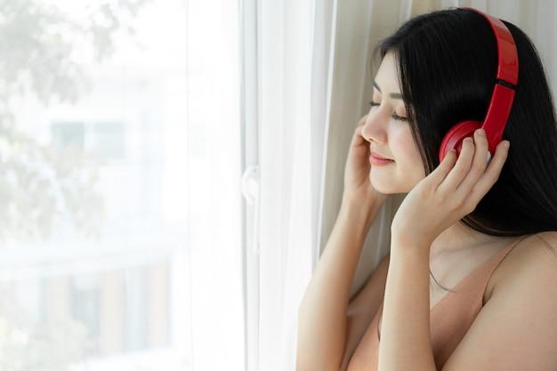 Das nette mädchen der schönen asiatischen frau des lebensstils fühlen sich glücklich genießen, musik mit kopfhörerkopfhörern auf weißem schlafzimmer zu hören Kostenlose Fotos