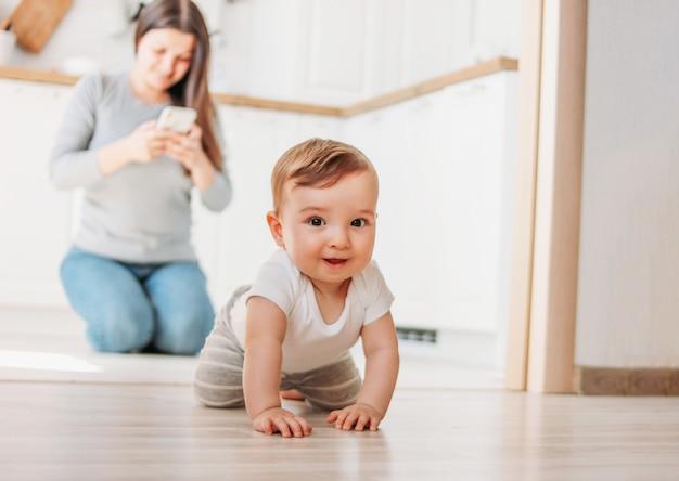 Das niedliche baby erforscht die welt, während mutter in ihrem smartphone in der küche surft Premium Fotos