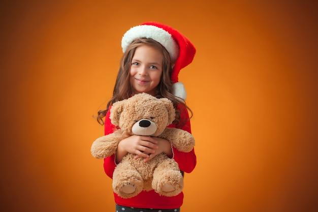 Das niedliche fröhliche kleine mädchen mit teddybär auf orange hintergrund Kostenlose Fotos