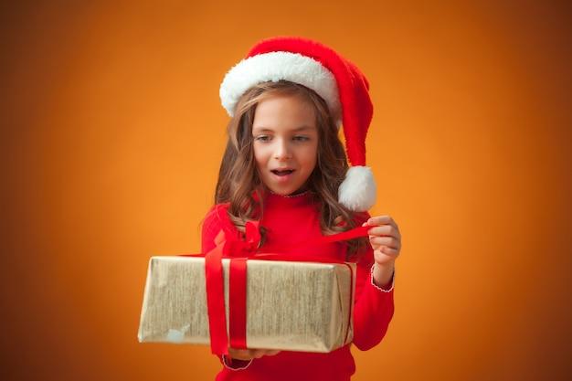 Das niedliche fröhliche kleine mädchen mit weihnachtsmütze und geschenk auf orange hintergrund Kostenlose Fotos