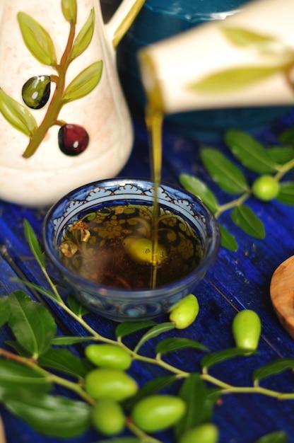 Das olivenöl in der tasse. zweig eines olivenbaums mit frischen oliven. grüne oliven. im garten. auf einem holzbrett. ein krug für öl. italienische klassiker. oliven aus italien. essen aus italien Premium Fotos