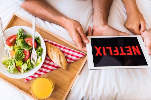 Das paar, das netflix aufpasst, zeigt nahe salat Kostenlose Fotos