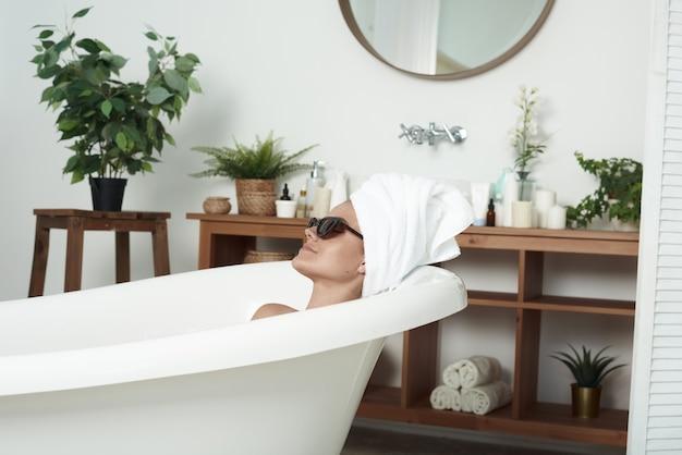 Das pathosschöne mädchen mit vitiligo liegt im bad in der sonnenbrille der katze und einem handtuch auf dem kopf. das konzept von mode, hautpflege und stil. Premium Fotos