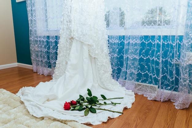 Das perfekte hochzeitskleid mit einem vollen rock im zimmerhochzeitskleid hält rote rose Premium Fotos