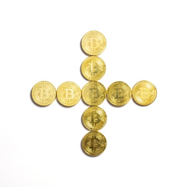 Das plus-symbol aus bitcoin-münzen gelegt und auf weißem hintergrund isoliert Kostenlose Fotos