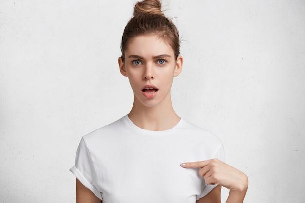 Das porträt der empörten schönen blauäugigen frau mit haarknoten, gekleidet in lässigem weißem t-shirt, zeigt an der leerstelle für ihr logo oder werbetext an, lokalisiert über weißem hintergrund. Kostenlose Fotos