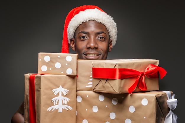 Das porträt des schönen jungen schwarzen lächelnden mannes in der weihnachtsmannmütze mit geschenken auf dunkelheit. Kostenlose Fotos