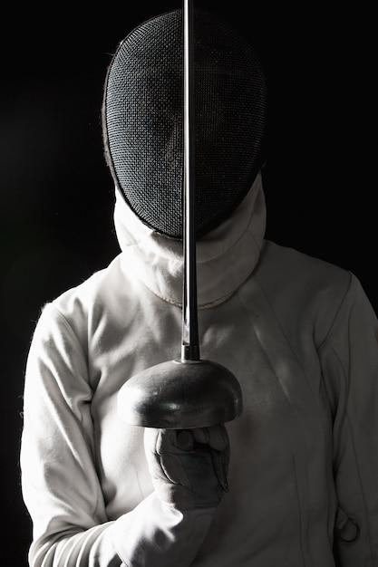 Das porträt des tragenden weißen fechtenkostüms der frau auf schwarzem Kostenlose Fotos