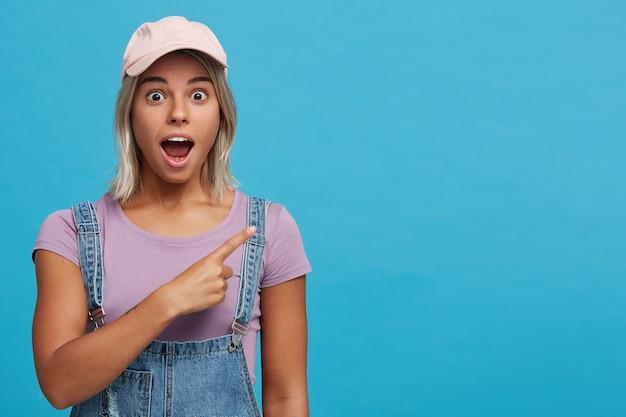 Das porträt einer erstaunten blonden jungen frau mit geöffnetem mund trägt eine rosa mütze, ein violettes t-shirt und einen jeansoverall. es ist schockiert und zeigt auf die seite, die über der blauen wand isoliert ist Kostenlose Fotos