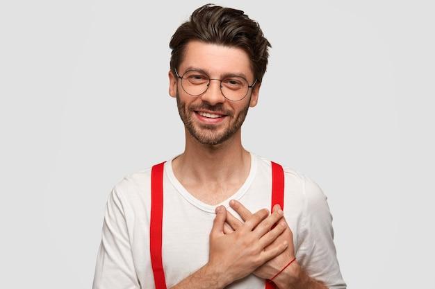 Das porträt eines glücklichen mannes hält beide handflächen im herzen, schätzt etwas mit großer dankbarkeit, trägt ein stilvolles outfit, hat ein freundliches lächeln, isoliert über der weißen wand. menschen, emotionen, positivität Kostenlose Fotos