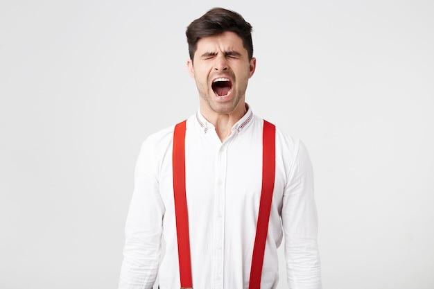 Das porträt eines gutaussehenden mannes wacht auf, gähnt mit geschlossenen augen, trägt hemd und rote hosenträger und hat nicht müde geschlafen Kostenlose Fotos