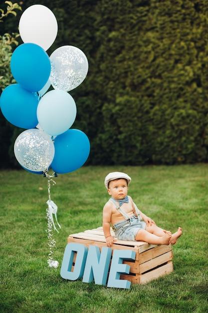 Das porträt eines hübschen kleinen jungen in stilvollen kleidern hat heute geburtstag Premium Fotos