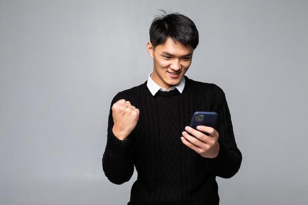 Das porträt eines jungen asiatischen mannes sieht glücklich aus, während eine gute nachricht auf dem smartphone auf weißer wand liest Kostenlose Fotos