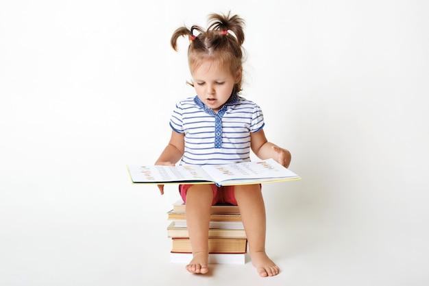 Das porträt eines kleinen entzückenden kindes sitzt auf einem stapel bücher, hält interessantes buch, betrachtet bilder, versucht, einige wörter zu lesen, bereitet sich auf die schule vor, isoliert auf weiß. kluges kleines mädchen Kostenlose Fotos