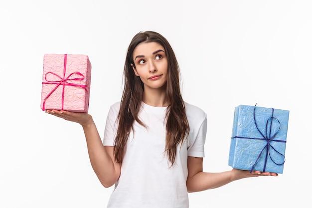 Das porträt eines nachdenklichen jungen mädchens, das eine entscheidung trifft, schaut verwundert auf und wiegt geschenkboxen in seitlich verteilten händen Kostenlose Fotos