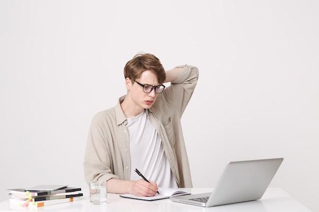 Das porträt eines nachdenklichen jungen studenten trägt ein beiges hemd und eine brille. es sieht konzentriert aus und studiert am tisch mit einem laptop und notizbüchern, die über der weißen wand isoliert sind Kostenlose Fotos