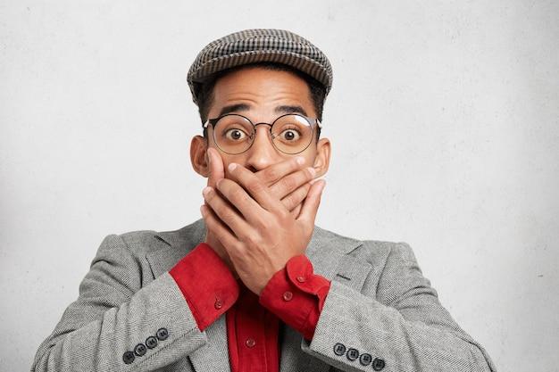 Das porträt eines überraschten besorgten mannes in einer brille bedeckt den mund mit beiden händen. Kostenlose Fotos