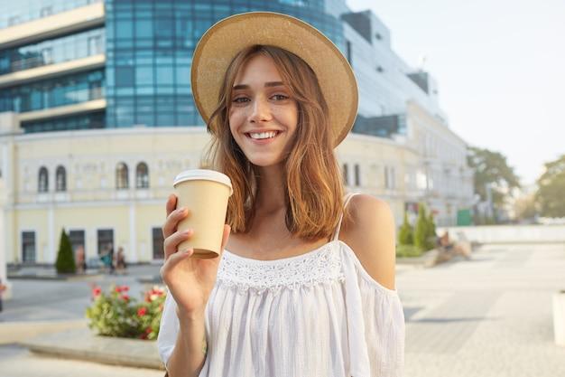 Das porträt im freien der fröhlichen attraktiven jungen frau trägt einen stilvollen hut, fühlt sich glücklich, steht und trinkt im sommer kaffee zum mitnehmen in der stadt Kostenlose Fotos